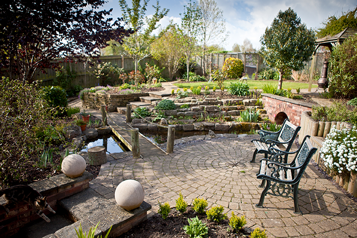 Sample backyard with stone patio, trellised planters, water feature and walkways.