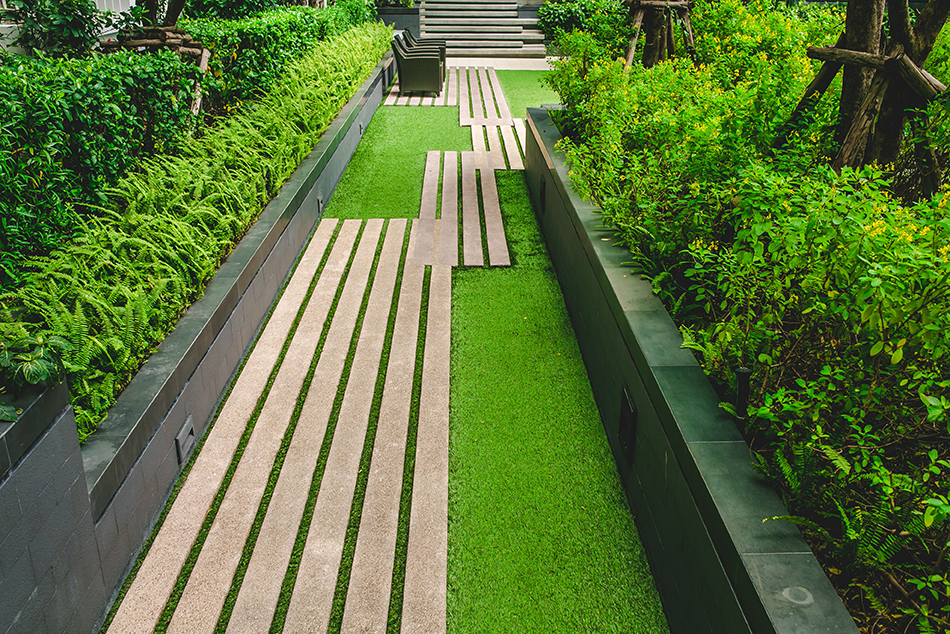 modern walkway over narrow grass backyard strip.